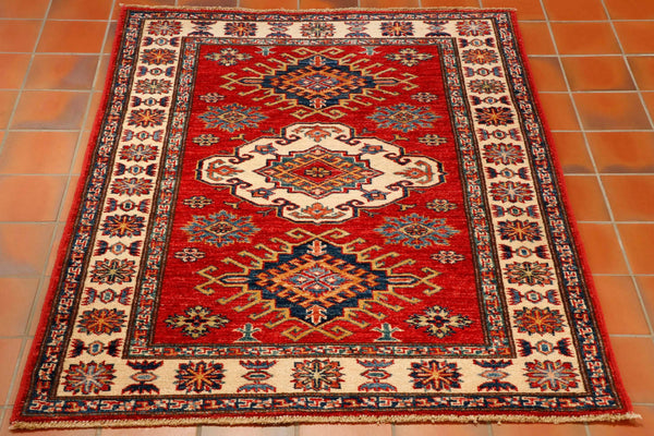 A traditional hand knotted Afghan Kazak made in Afghanistan using a Caucasian design. The rug is made from wool pile on to a cotton foundation. The colours used are a strong brick red for the background, a cream border and other colours include, both light and dark blue, gold and a sea green.