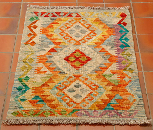 100% wool hand woven Afghan kilim in grey, gold and tangerine, with touches of turquoise, green and purple.