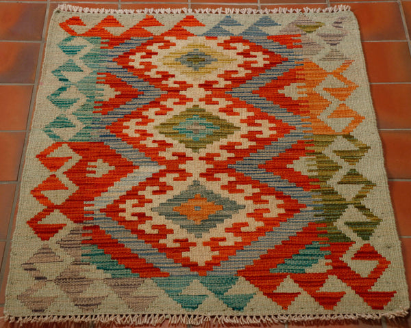 Colourful Afghan kilim with beige background and colours of flame orange, pale blue, olive green, tangerine , teal and mushroom.