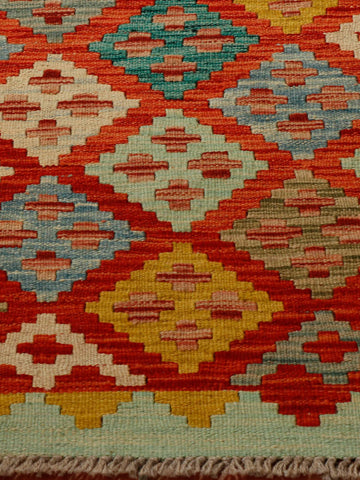 Afghan kilim with vibrant flame orange colouring and old gold, peppermint green soft blue and a teal shade.