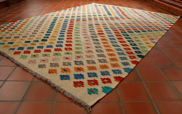 On a honey cream background, colours of gold, blue, green, terracotta and lilac has been woven in to a modern design kilim.