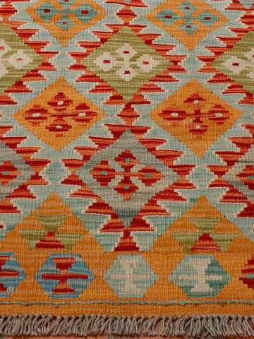 Geometric design with colours of tangerine, terracotta, flame red, olive green and grey used in this kilim.