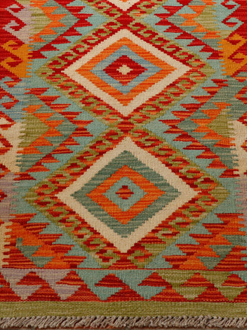 This lovely Afghan kilim runner has a striking geometric diamond design in colours of orange, teal and flame red.