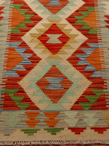 colourful kilim in terracotta, gold, flame red, duck egg blue, cream, grey and pale blue.