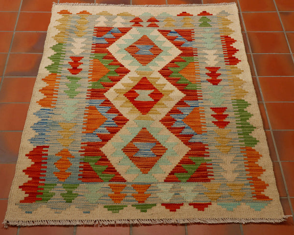 colourful kilim in terracotta, gold, flame red, duck egg blue, cream, grey and pale blue.  Edit alt text