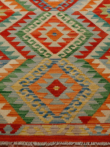 Different shades of green, terracotta and gold make up the colourings of this Afghan kilim.