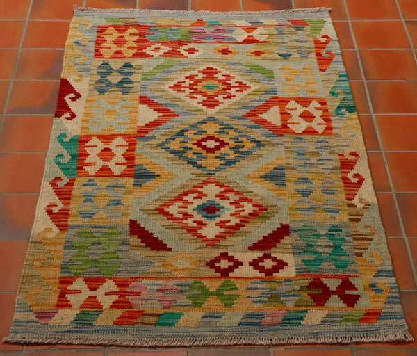 bright cheerful kilim using terracotta, pale green and bright green, blue, gold and burgundy colourings.