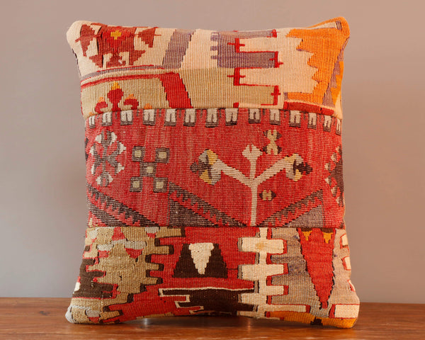 Patchwork kilim cushion with soft colourings of red, gold, brown and cream.