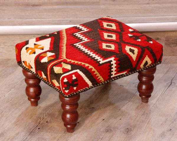 Small Turkish kilim stool with red, brown, cream and gold colours.