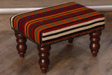 kilim covered stool covered in stripes of wine red, bright orange, black, gold and green