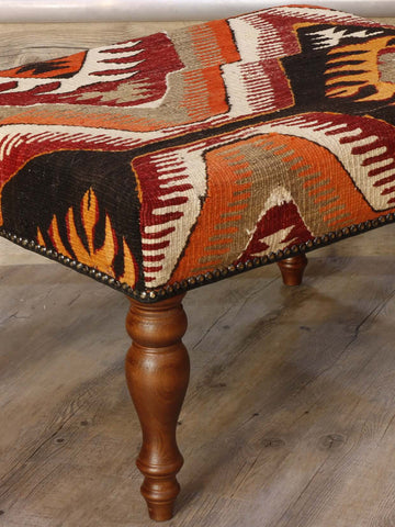 Turkish kilim stool in rich autumnal shades of orange, gold, red, cream and dark brown.