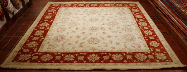 Square rugs and carpets are always very difficult to find. The background colour of this piece is cream and so tomis the outside edge. The main border is a strong rusty terracotta. This colour is also used to outline some of the floral design in the main ground. The carpet is made from wool pile on to a cotton foundation.