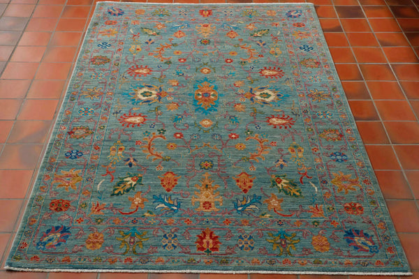 This Haji Jalili measures 189 by 127 centimetres.  The background colour of this piece is a beautiful smokey blue shade with accent colours of red, green old gold, turquoise, latte and denim blue. Some of the patterns are done in pale grey and outlined in pink which gives off almost a sort of heather tone. The decoration consists of intertwine stems, and flowers. There is a small central floral depiction and a border with further stylised flowers shown, laid out evenly around it.