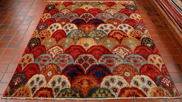 Well, this fine quality hand made Afghan rug is a true kaleidoscope of colour. Across the entire surface of this rug the pattern is that of overlapping scales. Each scale has its own internal decoration in a contrasting set of colours but from the same colour palette. There are many different shades of colour in this piece ranging from the deep dark red to the softer tones of red and the old gold, tan, light blue, navy blue, deep sea green, pale grey and cream to name but a few.