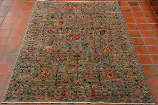 A pretty rug in modern colourings. The background is made up of a mottled shade, varying from soft grey to sage green-brown colour.  The accent colours which are red, gold, turquoise, amber, blue cream depict stylised flora and fauna with interlocking stems.  The border with the same ground colour has smaller trees and flowers held within it.  A practical hard-wearing rug suitable for any room in the home.