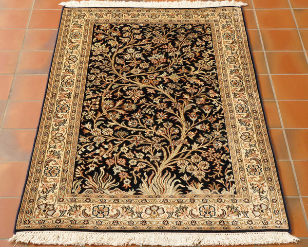 A very dark blue ground with cream borders of varying widths.  The delicate and intricate flora and fauna design covers the entirety of the rug using a colour palette of greens, browns and orange highlights.