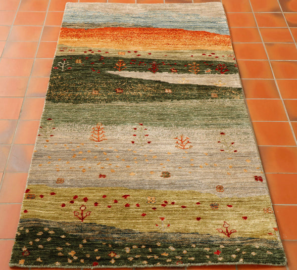 This is a hand knotted Afghan Gabbeh runner. It is really in between, a bit short for a runner and not quite wide enough for a rug of that length. The pattern is a landscape showing the different terrain in many shades of green, oatmeal, gold, terracotta and pale blue for the sky at the top.