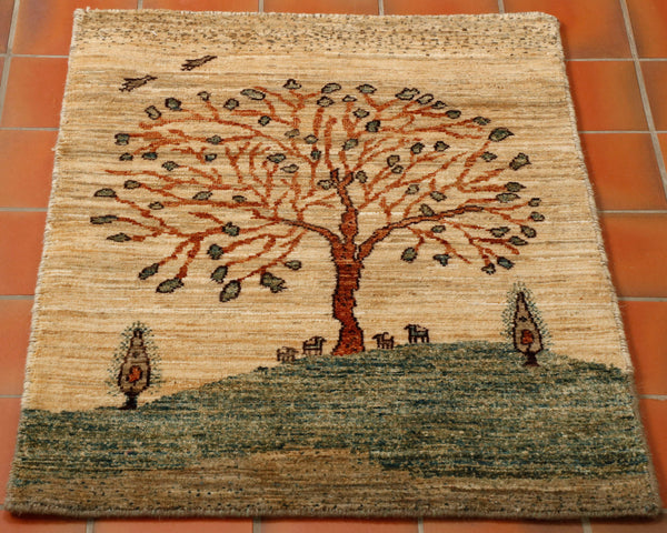 Unusual pattern and colouring with a tree of life design with animals and birds in oatmeal colour with green and brown. A little rug with huge appeal and character. There are even birds in flight over the tree.