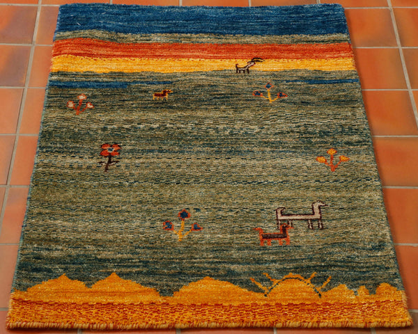 Afghan Gabbeh made in the style of the Persian Gabbeh rugs with random animals and flowers on a green background with old gold, orange and blue. Lovely quality rug with interest and character.