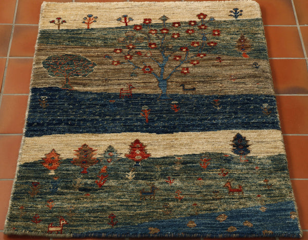 A little rug with bags of character. The design is a landscape depicting land and water with different types of trees and grazing goats. The rug is made from 100% hand spun vegetable dyed Afghan wool. This piece has no fringe and is bound with a barber pole effect on all four sides.