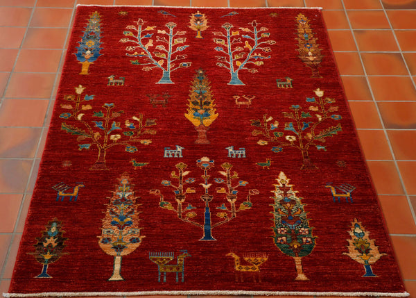 This is a hand knotted rug woven in Afghanistan with a wool pile. The foundation is cotton and it has a short cotton fringe. The background colour is a beautiful rich red and the design is a fairly primitive one with differing styles of trees and random stylised goats and birds. The other colours are old gold, sand, tan, and different shades of blue including turquoise .