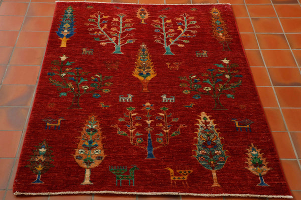 Stunning Afghan Shahi with warm red background and covered in lots of different trees in varying colours of gold, turquoise, blue, green and tan. Random stylised birds and animals have been added to give extra character.