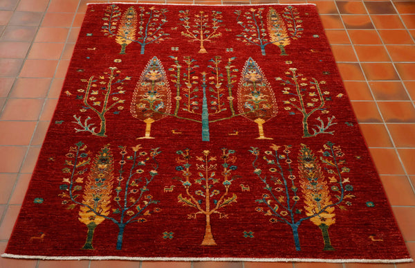 Crafted in Afghanistan, this stunning fine quality hand made rug is a real work of art. The design has much more of a modern feel to it. The vibrant red background is covered with different styles of interesting trees. The other colours used are blue, gold, green, tan and even some touches of turquoise.