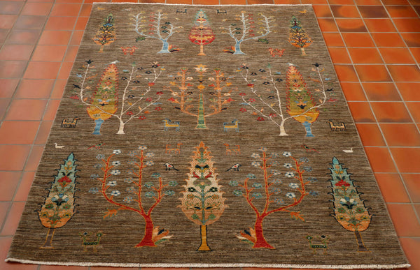 Although this Afghan rug has been made using traditional methods, the design is definitely more modern. The background colour is a mottled shade of donkey brown/sage green. The other shades used in the design range from gold, green, terracotta, beige, turquoise and cream. The background is covered in many different types of trees and some random stylised goats and peacocks thrown in for good measure.