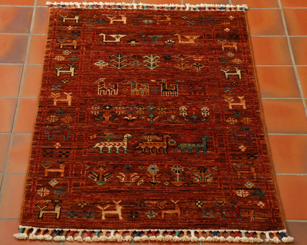 An unusual tobacco brown background hand knotted wool Afghan Samarkand rug covered with stylised goats and flowers. A little rug but with heaps of character. Something that would keep small children occupied for hours.