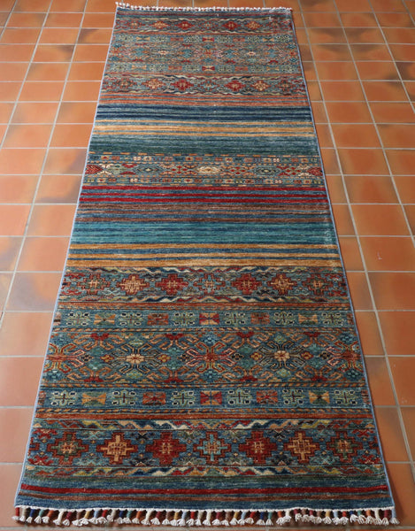 A great colouring has been used in this fine quality Afghan Samarkand runner. Predominantly different shades of blues, with old gold, tan, red and soft brown have been worked in to the design. The traditional geometric design is interspersed with plain bands of colour giving the piece a striking modern twist.