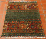 This is a small rug sized 121 by 77 centimetres.Wonderful colours used in this Afghan Samarkand rug with the main colour being a mottled racing green shade coupled with rust, gold, peach, cream and blue tones in the traditional design on the ends of the rug.   There are two large bands of decoration at either end of the rug incorporating various stylised flowers, hooks and large rhombi with internal decoration..  This piece also has the coloured wound fringes.
