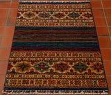 This is a small rug sized 120 by 79 centimetres.  Made up of part traditional design and part modern with the introduction of the plain stripes. The predominant colour of this lovely rug is the dark blue which is mixed with rust, gold, red, green and cream.  The decoration of the two brand bands at either end being a mix of large and small colourful, stylised flowers.