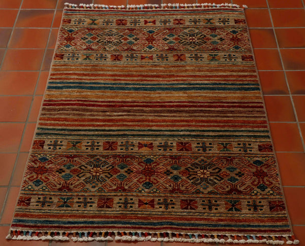 This is a small rug sized 128 by 80 centimetres.  The background shade is a coffee colour and it is combined with rust, teal, gold, red and brown in the stripes and patterned sections at either end with stylised flowers.