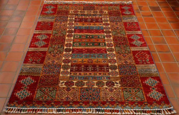 An unusual Hand knotted rug from north west Afghanistan. This is not a traditional design but made up of stripes, blocks and panels with flowers and plants in the central section. The colours are a mix of red, cream, green, blue, gold, orange and burgundy.