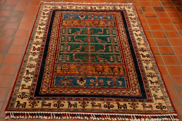 A hand made Afghan rug with a modern design. The main border is cream with stylised goats in it. The main body of the rug has wide bands of green, gold and blue with peacocks. This is a very striking rug and it is finished off with a fancy multi coloured fringe.