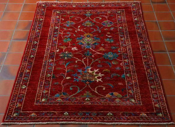This small piece measures 149 by 100 centimetres. The opulent, red background is a great colour to show off the other colours in the main section of the rug with it's larger floral decoration. More smaller floral decoration can be found in the borders. The colours include vivid turquoise, olive green, denim blue, terracotta, mocha and even touches of purple. This rug has the added feature of not being symmetrical.