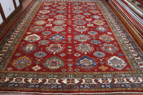 A fabulous Fine Kazak, 399 by 291 centimetres in size.  It comes with a rich red background, and bold geometric pattern in colours of light and dark blue, tangerine, cream and a bluey-green, terracotta and rust.  The borders a mix of the same palette , 5 bands deep with smaller geometric designs within each band.  The fineness of the detail is a sign of high-quality weaving.