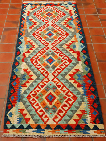 Afghan kilim runner measuring 200 by 70 centimetres with a palette of striking vivid colours including poppy red, soft turquoise, olive green, pale lemon, cream and edged in a navy blue. The central panel is a series of lozenges of increasing sizes flows through the middle of this piece, combined with a dark blue zig zag edge with small decorative rhombi in poppy red as a feature.  A mixed band of toured zig zag again with decorative blue rhombi butts up to the blue edge.