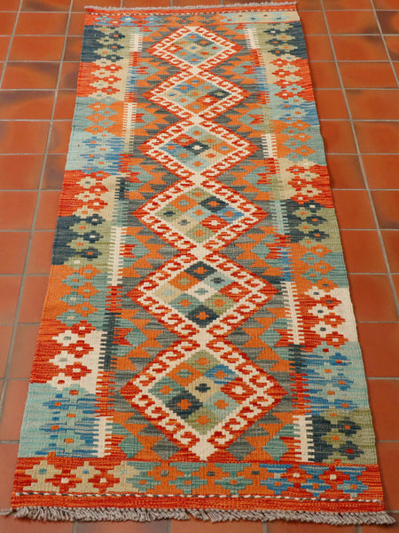 Lovely Afghan kilim runner measuring 188 by 63 centimetres with really great colours of terracotta, light and dark blue, cream and pale green. The design is very traditional with large geometric diamonds with each one containing a chequer board made up of a mix of the colour palette within through the centre, and smaller decorative motifs around the edges. The colours blend together at the edges of each section.