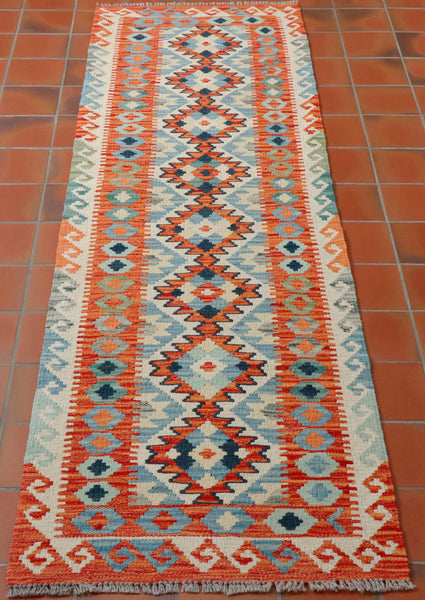 Lovely Afghan kilim runner measuring 208 by 62 centimetres in soft terracotta, soft green and blue shades, with cream and terracotta backgrounds. The design is very traditional with large geometric diamonds through the centre, and smaller hook and lozenge decoration around the edges.  This piece is slightly longer than most in relation to the width.
