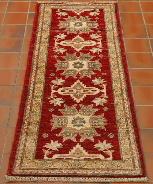 This short runner is made by Afghan weavers using vegetable dyed wool on a  cotton foundation. it is predominantly red with neutral ground borders