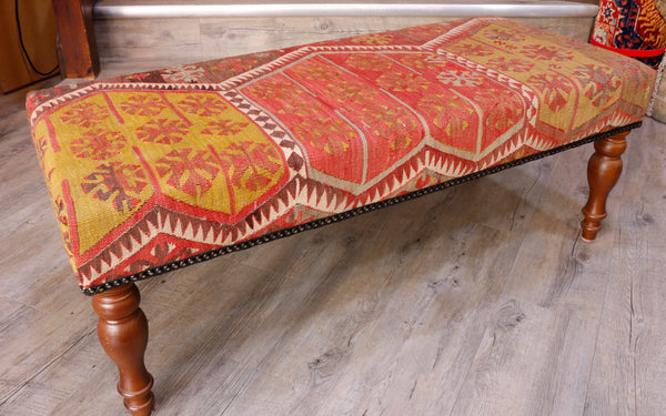 "The finely woven Turkish kilim used on this bench has beautiful muted colourings of dusky pinky/red, old gold, soft brown and cream. The kilim has some age to it but is in excellent condition and it has a genuine old ""antique"" look.  The design consists of geometric shapes some of which are almost snow flake in their style."