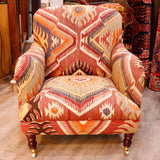 The Howard chair is a timeless, classic country house design. The fact that this chair has been covered in old Anatolian kilim means that is it colourful, comfortable and very durable. Often the colours in the old kilims have toned down and the fabric has softened making it more malleable for working with.   This is a dramatic piece.  There is almost a sense of dancing flames and eyes within the design.
