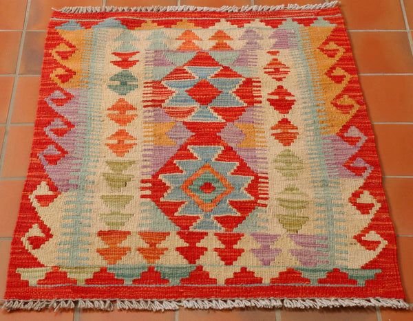 Size 84 by 60 centimetres. A small, bright coloured Afghan kilim in a traditional geometric design. The colours are quite wacky and will certainly make a statement. There is a mix of bright reds and oranges, pale blue, soft green, sea green and a heathery lilac shade for contrast.