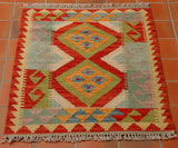 Size 90 by 65 centimetres. A small, bright coloured Afghan kilim in a traditional geometric design. The colours are quite wacky and will certainly make a statement. There is a mix of bright reds, mid blue, pale blue, leaf green, sea green, soft yellow, cream and a heathery lilac shade for contrast.