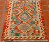 Size 100 by 60 centimetres. A small, bright coloured Afghan kilim in a traditional geometric design. The colours are quite wacky and will certainly make a statement. There is a mix of bright oranges, pale blue, mid blue, soft green, sea green and a heathery lilac shade for contrast.