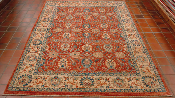 This is a highly decorated piece with William Morris type decoration upon it.  Each flower is linked by stems and leaves.  The main area of the rug is on a terracotta ground with contrasting blue, cream and soft green flowers.  Meanwhile the border is on a cream ground again with flowers upon it using the same colour palette.  Throughout the shade of blue used is a striking bright blue with a hint of turquoise.