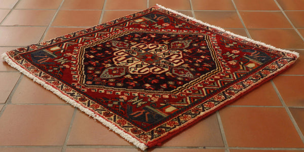 small square mats from Iran can be very useful in providing brights spots of colour, often used on sub landings and doorways. The traditional hand knotted piece is cherry red with smokey blues, the central design is framed by the horse heads of Persepolis
