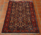 This is a lovely little Persian rug in traditional design and colours. The background is dark blue and is covered with a small allover design based on flowers. The border is red with flowers all the way round. The pile is made from wool and has a sheen on it and is on a cotton foundation. This piece has a very short white fringe at either end.