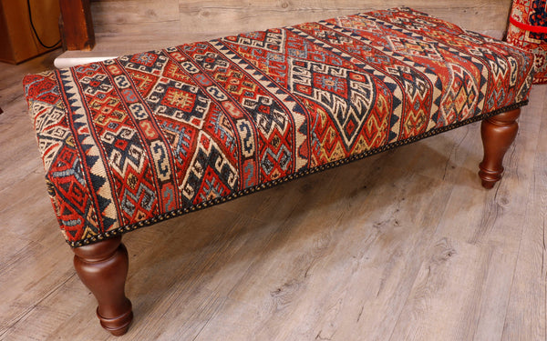 This is a beautiful example of a Soumak weave with the fine embroidery work done in different shades of blue, gold, cream and brick red. This is by far the nicest bench stool that we have had in long while.  The design consists of varying width bands of interlocking geometric designs.  The central band being the largest and most dramatic.